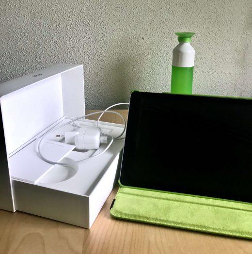 Een foto van een tweedehands iPad op een neutrale achtergrond. Met doos, boekje en lader duidelijk zichtbaar