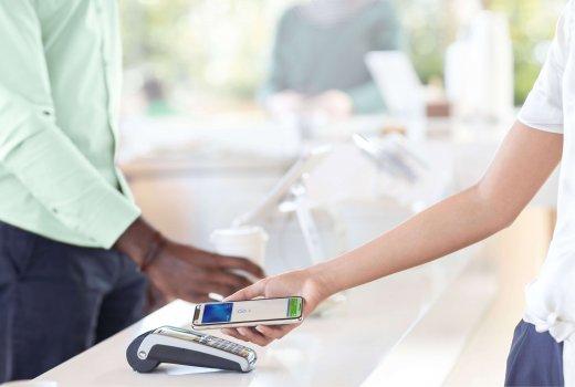 Een vrouw houdt haar iPhone naast een pinapparaat om te betalen met Apple Pay